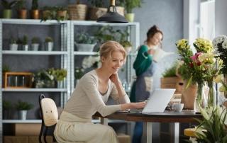 woman in flower shop on laptop