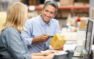 Man scanning a package with female coworker